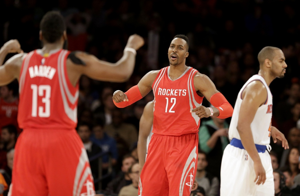 Houston Rockets' Dwight Howard, center, celebrates with James Harden, left, while New York Knicks' Arron Afflalo walks away during the overtime period of the NBA basketball game against the New York Knicks, Sunday, Nov. 29, 2015, in New York. (AP Photo/Seth Wenig)
